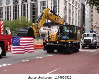 New York City, New York / USA - September 08 2018: An American flag patriotically displayed from the bucket of a backhoe during the New York City Labor Day Parade.