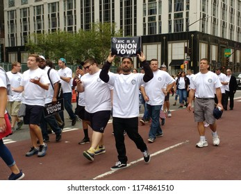 """New York City, New York / USA - September 08 2018: A marcher carries a sign stating that, """"NYC Is A Union Town"""" during the New York City Labor Day Parade."""