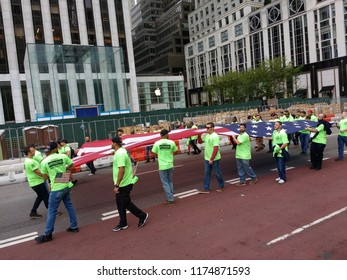 New York City, New York / USA - September 08 2018: Union workers carry an enormous American flag during the New York City Labor Day Parade.