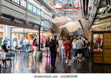 New York City, USA - September 21, 2019: People walking along shops inside the historic Chelsea Market.