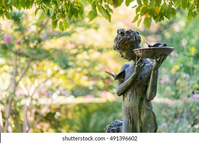 New York City, USA - September 24, 2016. Sculpture of a girl with a bird bath at the Burnett Memorial fountain. Natural setting with a bronze fountain statue in Conservatory Garden, Central Park.