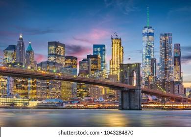 New York City, USA skyline on the East River with Brooklyn Bridge at dusk.