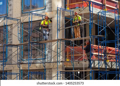 New York City, New York / USA United States - 04 08 2019: Construction workers at work on a skyscraper building renovation and construction site on a scaffold