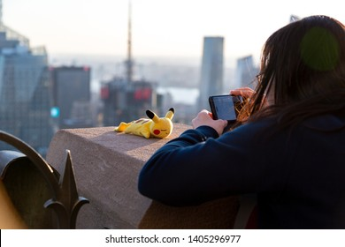New York City, New York / USA United States - 04 08 2019: Asian girl taking a picture of Pokemon character Pikachu toy with New York City Manhattan panorama.