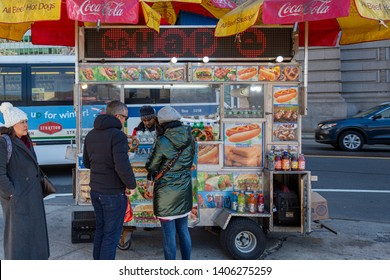 New York City, New York / USA United States - 04 08 2019: People buying pretzels and Coca Cola from New York street fast food truck.