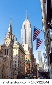 New York City / New York , USA United States - 04 08 2019: View of Empire State Building and Marble Collegiate Church with American flags from 5th Avenue 28th st