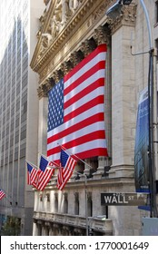 New York City, USA-October 2009; Side view of the facade of the New York Stock Exchange (NYSE) covered in a giant American flag; street sign Wall Street in foreground