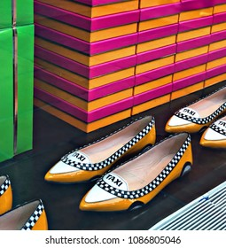 NEW YORK CITY,  View of a designer pairs of fashion flat shoes with a New York yellow taxi cab design in the window of a Kate Spade store by Rockefeller Center in New York City (2018/03/29)