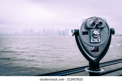 New York City viewfinder binoculars. A traditional tourist viewfinder on Liberty Island looking towards the NYC skyline on a grey and overcast day.