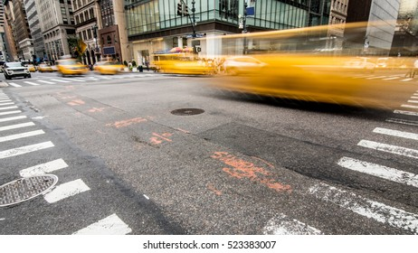 New York City Yellow cabs blurred passing by the camera on a NYC intersection, no logos or recognizable people