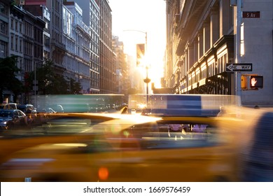 New York City yellow taxi cabs speeding through the intersection of 23rd Street and 5th Avenue with sunlight shining between the background buildings in Midtown Manhattan NYC