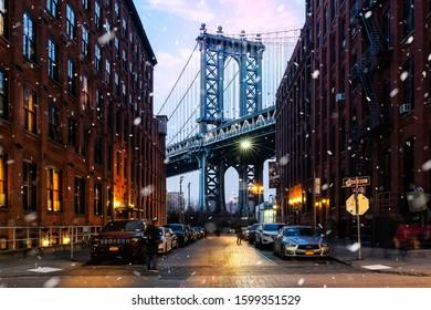 New York City, New York/USA - December 11, 2018: The Brooklyn Bridge from Dumbo shot from an alleyway with snow falling with people walking by and parked cars on the side of the road.