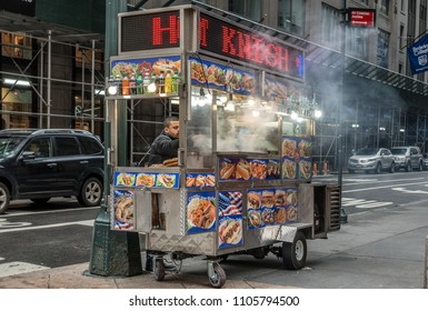 New York City,NY,USA on 12th May2018;Street food vendor selling conveniant fast food on 5th Ave in New York City. Pretzels,hot dogs and other fast food items are cooked and served from carts across NY