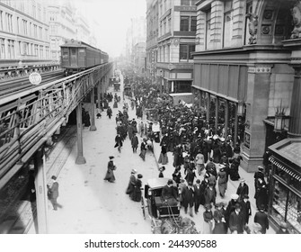 New York City's Sixth Avenue crowded with shoppers in 1903. Horse drawn carriages and wagons travel on the street level as an elevated train passes above.