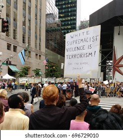"""New York City/USA August 14 2017: A demonstrator near Trump Tower holds a sign that says, """"White Supremacist Violence Is Terrorism! Say The Words, Donald!"""""""