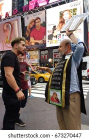 """New York City/USA July 2 2017: A young man wearing a bracelet that says """"Palestine"""" argues over religion with a preacher in Times Square."""