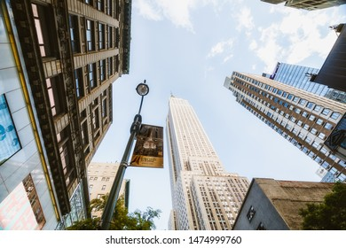New York City/USA -May 27, 2019 Empire State Building and Skyscrapers, New York City. Low Angle View, Blue Sky Background, Perspective