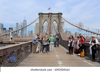 New York City,USA,05.07.2018. Photo of the iconic Brooklyn Bridge with many happy tourists walking and relaxing on it,with blue sky and cityscape on the background.