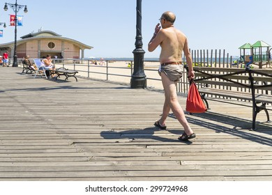 NEW YORK CITY,USA-AUGUST 6,2013:people stroll among the shops of coney islan admiring the sea and tanning in the sun