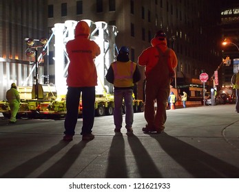 NEW YORK - DEC 12: Workers use a large truck to move a piece of the spire of One World Trade Center early on December 12, 2012 in New York City. The spire was manufactured in sections in Canada.