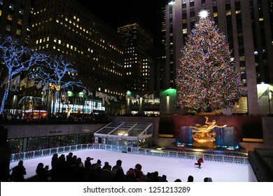 NEW YORK - DECEMBER 4, 2018: A brightly illuminated Rockefeller Plaza with a Christmas tree. The ice skating rink filled with tourists skating on December 4, at NYC, NY.
