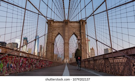 New York, early morning at the Brooklyn bridge with a biker on empty Brooklyn bridge heading towards  Manhattan skyline and earphone souvenirs left from tourists on the left side on the bridge