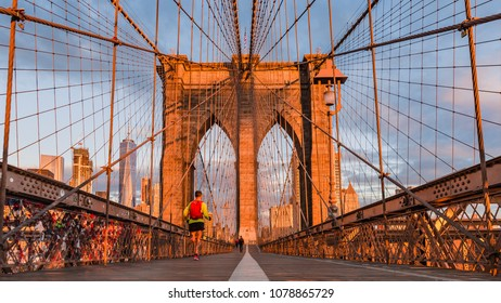 New York, early morning glow at the Brooklyn bridge with the back of a runner on a fast empty Brooklyn bridge heading towards  Manhattan skyline