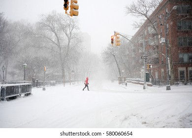 NEW YORK - FEB 9: A pedestrian walks across Waverly Place as snow falls on February 9, 2017 in New York. Snowfall totals of approximately six inches fell in and around NYC.