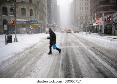 NEW YORK - FEB 9: A pedestrian walks across Broadway as snow falls on February 9, 2017 in New York. Snowfall totals of approximately six inches fell in and around NYC.