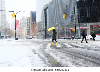 NEW YORK - FEB 9: Pedestrians walk along Astor Place as snow falls on February 9, 2017 in New York. Snowfall totals of approximately six inches fell in and around NYC.