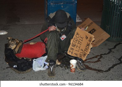 NEW YORK - FEBRUARY 25: A homeless man sitting on the street with a dog and asking for help February 25, 2012 in New York City.