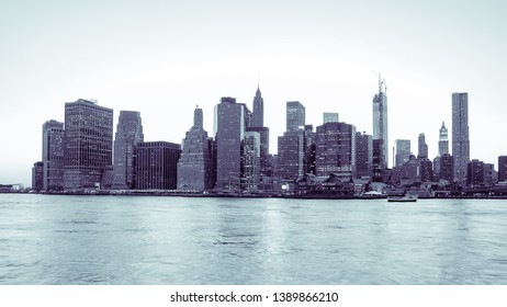 New York Financial District and the Lower Manhattan at dawn viewed from the Brooklyn Bridge Park. Blue black and white image.