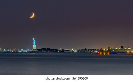 New York harbor by night with a crescent moon over the Statue of Liberty