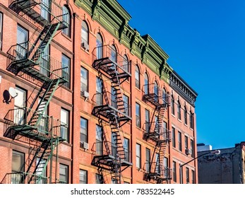 New York Harlem typical building facade with fire escape stairs and blue sky