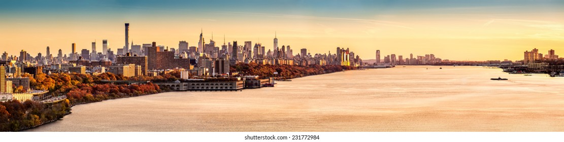 New York and Hudson River panorama as viewed from George Washington Bridge at sunset. Manhattan buildings reflect an orange glow from the last rays of the day.