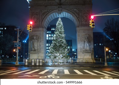 NEW YORK - JAN 3, 2017: red traffic lights at crosswalk on Washington Square Park North with Christmas tree under arch at night in NYC. WSP is among the most popular of the city's 1,900 public parks.
