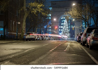 NEW YORK - JAN 3, 2017: Washington Square Park North arch and Christmas tree lights on holiday night on Lower 5th Ave in NYC. The famous monument is an homage to France's Arc de Triomphe in Paris.