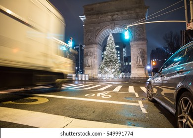 NEW YORK - JAN 3, 2017: truck motion blur driving down lower 5th Ave toward Washington Square Park arch with Christmas tree lights at night in NYC. WSP is a located in Greenwich Village in Manhattan.