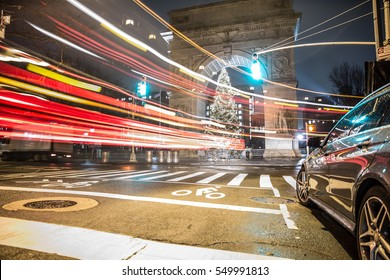 NEW YORK - JAN 3, 2017: beautiful long exposure of traffic, car streaks on Lower 5th Ave with Christmas tree at Washington Square Park North at night in NYC. WSP is a popular space in New York City.