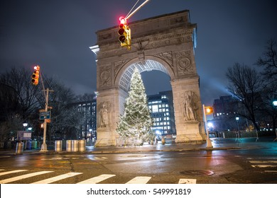 NEW YORK - JAN 3, 2017: beautiful lit up Christmas tree Washington Square Park arch at night with red traffic lights on Lower 5th Ave crosswalk in NYC. 5th Avenue is a major thoroughfare in Manhattan.