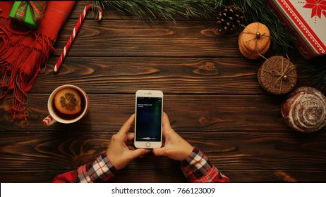 NEW YORK - January 08, 2017: social media. Siri app. View from above. Woman using Siri application on the white smart phone surrounded by Christmas atmosphere. Brown table with Christmas decorations.