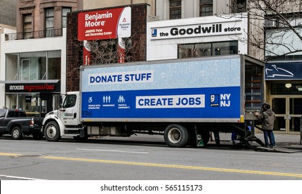 New York, January 21, 2017: Two employees are unloading a Goodwill truck is parked in front of their store.