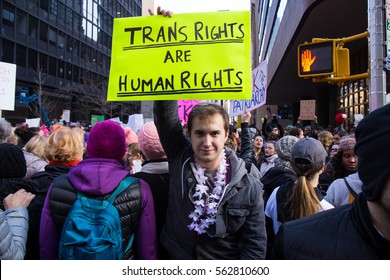 "NEW YORK - JANUARY 21: An unidentified man holds a sign that reads ""Trans Rights Are Human Rights"" at the Women's March on New York City on January 21, 2017 in New York."