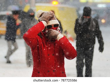 NEW YORK, NEW YORK- JANUARY 4TH, 2018:  People in Times Square brace against the cold as a  winter blizzard called a Bomb Cyclone hits New York City.