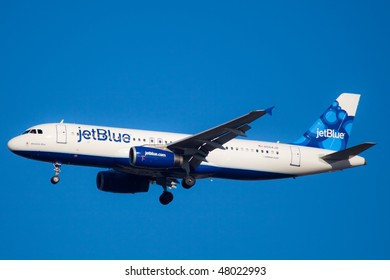 """NEW YORK - JANUARY 9: An Airbus A320 jet Blue with new tail design """"blueberries""""  lands at JFK Airport on Runaway 31R on January 9, 2010 in New York."""