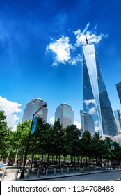 NEW YORK, NEW YORK - JUL 6: The World Trade Center Memorial with World Trade Center One in background on July 6, 2018. The park memorializes 9/11 attack on the United States.
