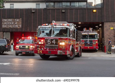 NEW YORK - JULY 13, 2017: Firefighters trucks leaving their fire station (Engine 54, Ladder 4, Battalion 9), to the streets of Manhattan of New York City on July 13th, 2017 in New York, NY, USA
