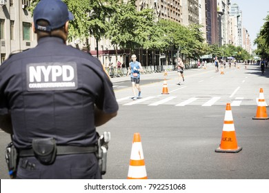 NEW YORK - JULY 16 2017: NYPD patrol the route on West 72nd St for athletes running the 10k portion of the Panasonic New York City Triathlon Race, the only International Distance triathlon in NYC.