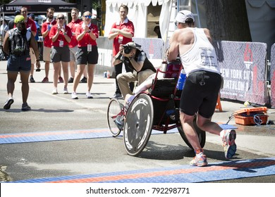 NEW YORK - JULY 16 2017: David and Blake Ferrell, father and son team, cross the finish line after completing the 1.5k swim, 40k bike, and 10k run of the Panasonic NYC Triathlon Race in Central Park.