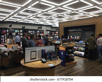 NEW YORK- JULY 2017: Amazon Books store clerk behind counter. Customers can pay w Amazon Prime in brick-and-mortar Time Warner Center. E-commerce biz sells Kindles, Fire TV tablet Alexa Echo AMZN